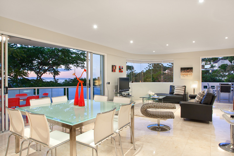 Dining table and open plan living looking out onto a beautiful sunset sky 1_8 noosa drive niche luxury accommodation