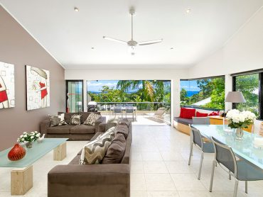 Open plan living area in Bayview Road looking through the windows to the ocean